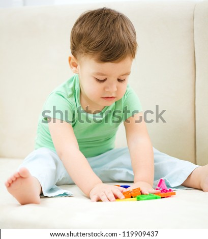 Cute little boy playing with toys while sitting on a couch, indoor shoot
