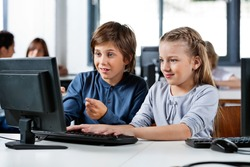 Cute little boy pointing while using desktop PC with friend at desk in school computer lab