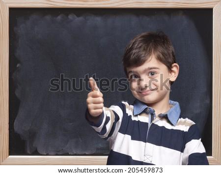 Cute little boy posing in front of a blackboard #205459873