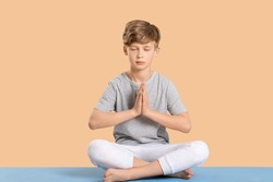 Cute little boy practicing yoga on color background