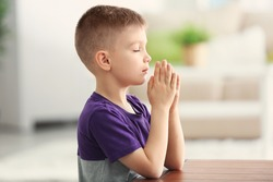Cute little boy praying at home
