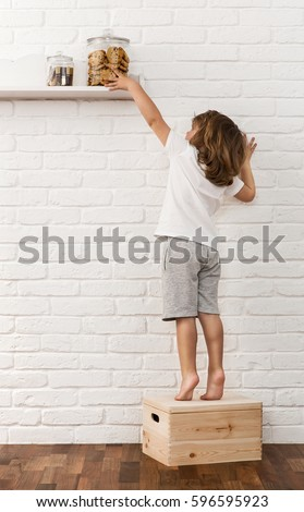 Cute little boy reaching for the chocolate chip cookies on the kitchen shelf