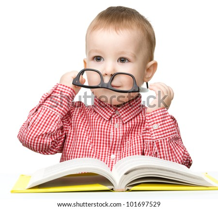 Cute little boy reads a book while sitting at table, isolated over white