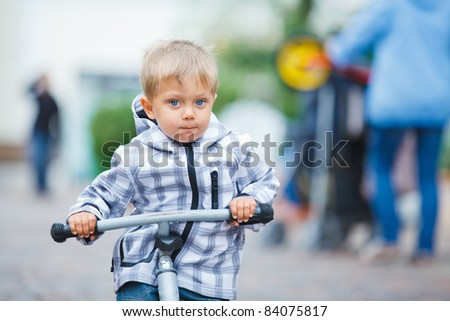 cute little boy rides his bike outdoors in city street
