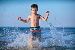 Cute little boy running through the water at the beach