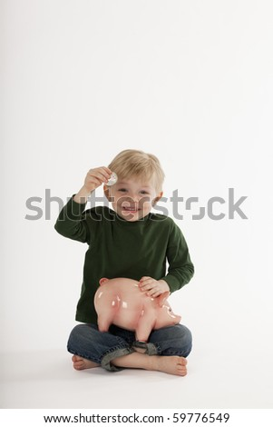 Cute little boy shows a large coin while holding a piggy bank in his lap. He is sitting cross-legged on the floor and smiling at the camera. Vertical shot.