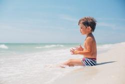 Cute little boy sitting at ocean beach