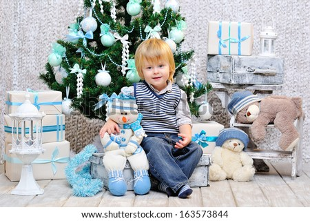 Cute little boy sitting down by the decorated Christmas tree with toys, teddy bears and gift boxes