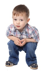 Cute little boy sitting isolated on white background. looking at camera. concept.