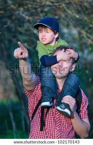 Cute little boy sitting on father's shoulders outdoors in city park
