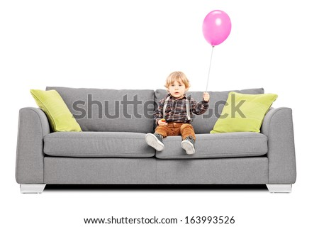 Cute little boy sitting on sofa with a hot air balloon isolated on white background
