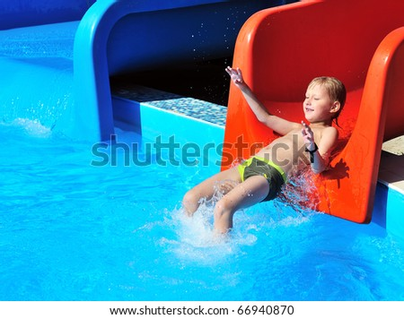 Cute little boy sliding down a water slide