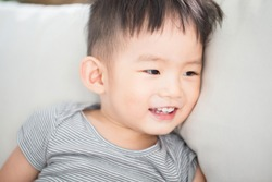 cute little boy smile happily and sit on sofa at home