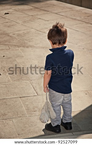 Cute little boy standing back and holding a stuffed toy