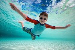 Cute little boy swimming underwater in tropical sea