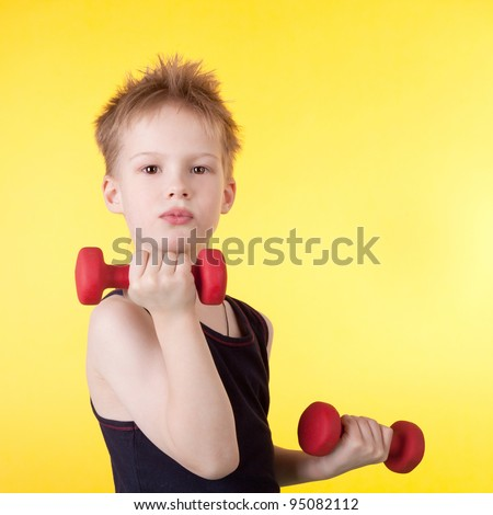 cute little boy training with the dumbbells