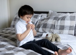 Cute little boy trying to close white polo shirt buttons, School Kid sitting in bed with teddy bear tried to button up his school polo shirt, Cute boy getting dressed and get ready for school,