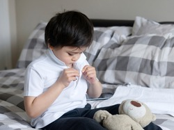 Cute little boy trying to close white polo shirt buttons, School Kid sitting in bed with teddy bear tried to button up his school polo shirt, Cute boy getting dressed and get ready for school.