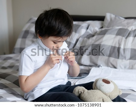 Cute little boy trying to close white polo shirt buttons, School Kid sitting in bed with teddy bear tried to button up his school polo shirt, Cute boy getting dressed and get ready for school. #1075138901