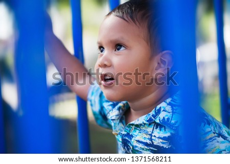 Cute little boy wearing a hawaiin print shirt and looking up with a positive facial expression while playing in an outdoor kids playground.