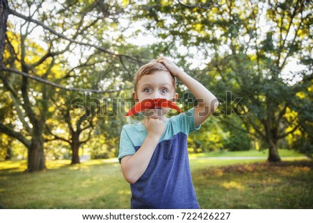 cute little boy wearing bright red mustache from autumn leaves. funny child with artificial mustache surprised #722426227