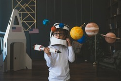 Cute little boy wearing cardboard astronaut helmet flying toy rocket through planets, cardboard spaceship rocket in the background
