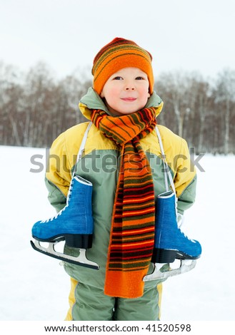 cute little boy wearing warm winter clothes going ice skating