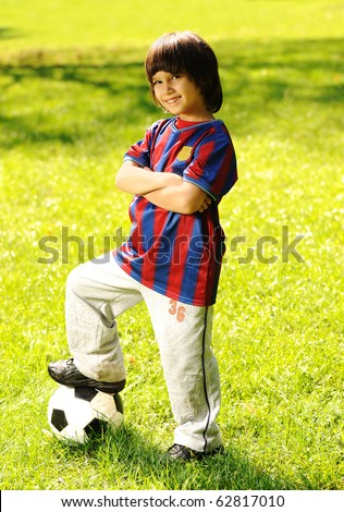 Cute little boy with a ball in beautiful park in nature
