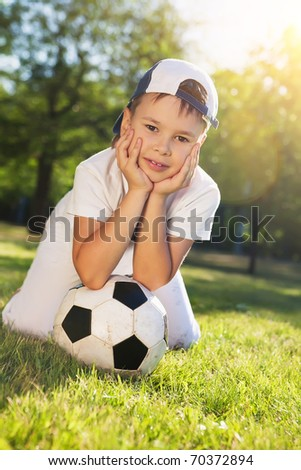 Cute little boy with a ball in beautiful park in nature;