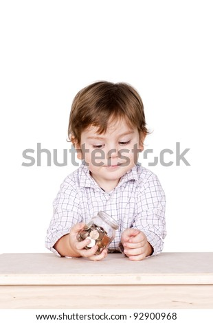 Cute little boy with a bottle in his hands with some coins in it. Isolated on white.