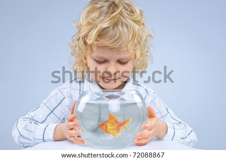 Cute little boy with a fish in an aquarium. In the studio