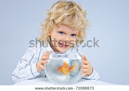 Cute little boy with a fish in an aquarium. In the studio - stock