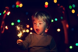 Cute little boy with a funny face holding sparklers. There is a background with multi colored lights. Image with selective focus and toning