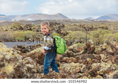 Cute little boy with backpack have trip in the mountains