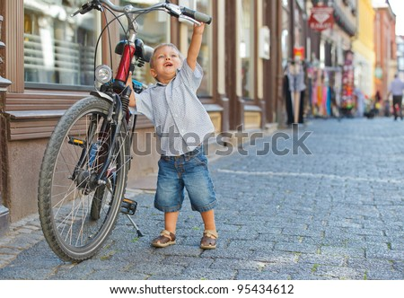 cute little boy with big bike outdoors in city street