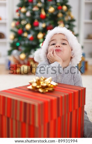 Cute little boy with big present, sitting in front of Christmas tree