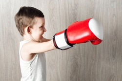 cute little boy with boxing gloves large size. Portrait of a sporty child engaged in box. fooling around and not serious. wooden background