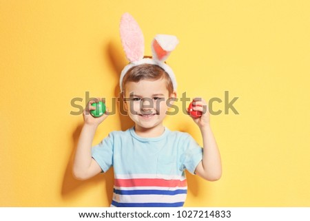 Cute little boy with bunny ears holding Easter eggs on color background #1027214833