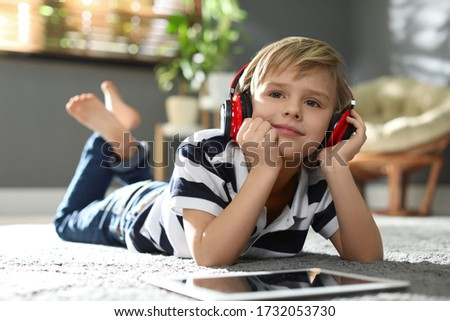Cute little boy with headphones and tablet listening to audiobook at home Stockfoto ©