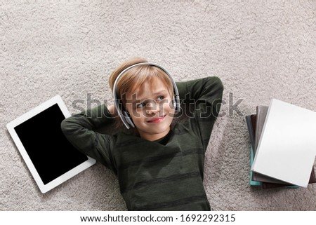 Cute little boy with headphones and tablet listening to audiobook on floor indoors, flat lay Stockfoto ©