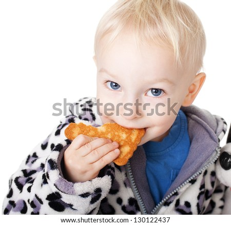 Cute little boy with his teddy eating a cookie isolated on white background