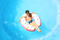 Cute little boy with inflatable donut in swimming pool