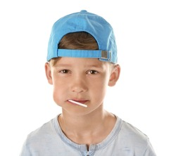 Cute little boy with lollipop in mouth on white background