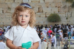 Cute little boy with long blond curls and blue eyes in knitted skullcap. He stands at the main Jewish shrine - Western Wall of Temple. The Jewish holiday of Sukkot