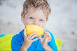 Cute little boy with mango fruit on the beach