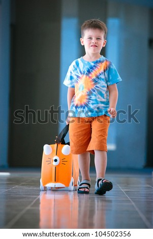 Cute little boy with orange suitcase at airport