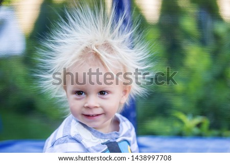 Cute little boy with static electricy hair, having his funny portrait taken outdoors on a trampoline #1438997708