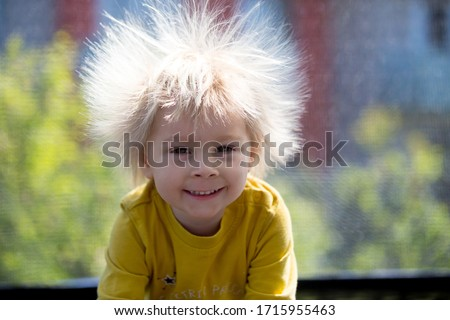Photo of  Cute little boy with static electricy hair, having his funny portrait taken outdoors on a trampoline