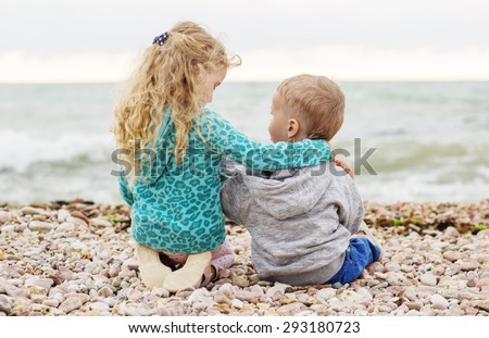 cute little brother and sister playing on the beach