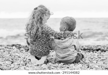 cute little brother and sister playing on the beach (  black and white )